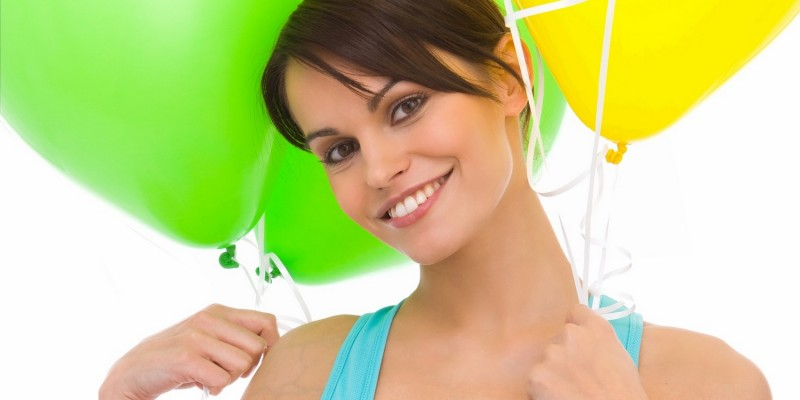 Frau hält grüne und gelbe Luftballons