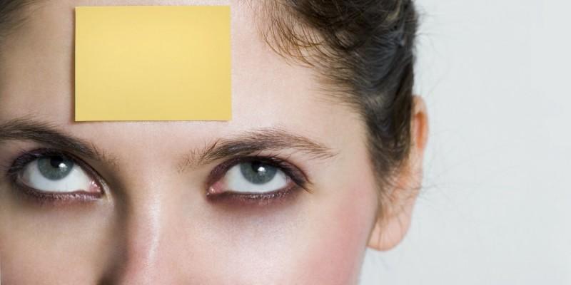 Frau mit Haftnotiz auf der Stirn
